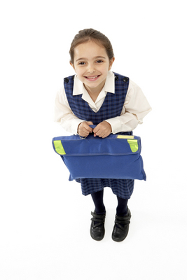 Studio Portrait of Smiling Girl Holding School Bag